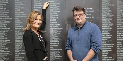 Left to right: Settlement Services International CEO, Violet Roumeliotis and Australian National Maritime Museum CEO, Kevin Sumption standing in front of the Welcome Wall