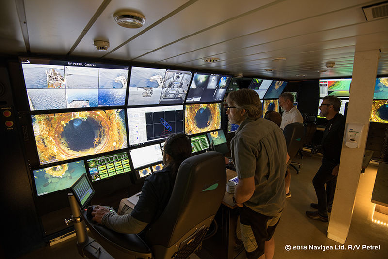 Expedition members participating in the 2018 ROV examination of AE1 watch live footage of the submarine's stern torpedo tube in the control room aboard the research vessel Petrel. Image: Paul G. Allen, Find AE1 Ltd., ANMM and Curtin University. Copyright, Navigea Ltd.