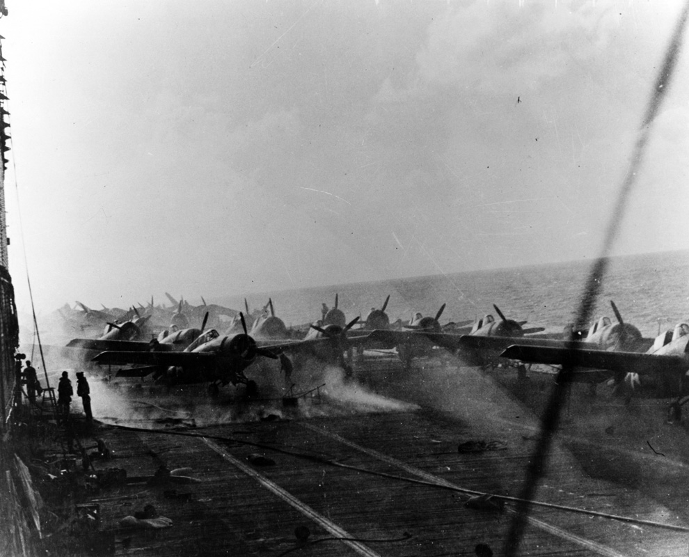 View on the flight deck of USS <em>Lexington</em>  on 8 May 1942, during the Battle of the Coral Sea. Smoke is rising around the after aircraft elevator from fires burning in the hangar. Image: Official US Navy photograph collection of the National Archives, Naval History and Heritage Command BD-G-16802.