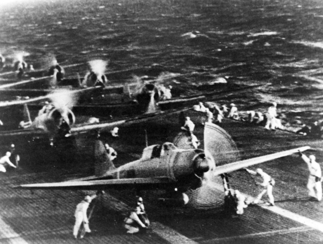 Japanese naval aircraft prepare to take off from an aircraft carrier (reportedly <em>Shokaku</em>) to attack Pearl Harbor during the morning of 7 December 1941. Plane in the foreground is a Zero Fighter. This is probably the launch of the second attack wave. The original photograph was captured on Attu in 1943.  . Image: Official US Navy photograph collection of the National Archives, Naval History and Heritage Command BD-G-71198.