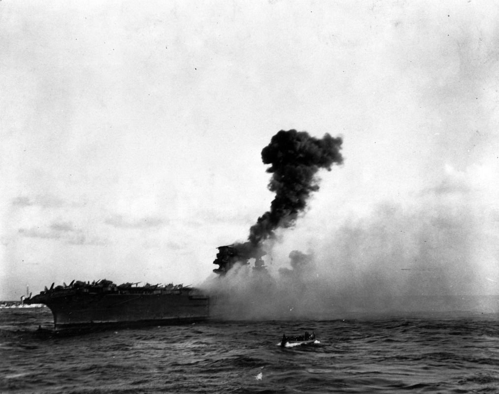 An explosion amidships on USS <em>Lexington</em> (CV-2), while it was being abandoned during the afternoon of 8 May 1942. This may be the explosion reported to have taken place at 17:27 hrs, which was followed by a great explosion aft as stowed torpedo warheads detonated on the hangar deck. Note whaleboat underway in the foreground. Image: Official US Navy photograph collection of the National Archives, Naval History and Heritage Command BD-G-7406.