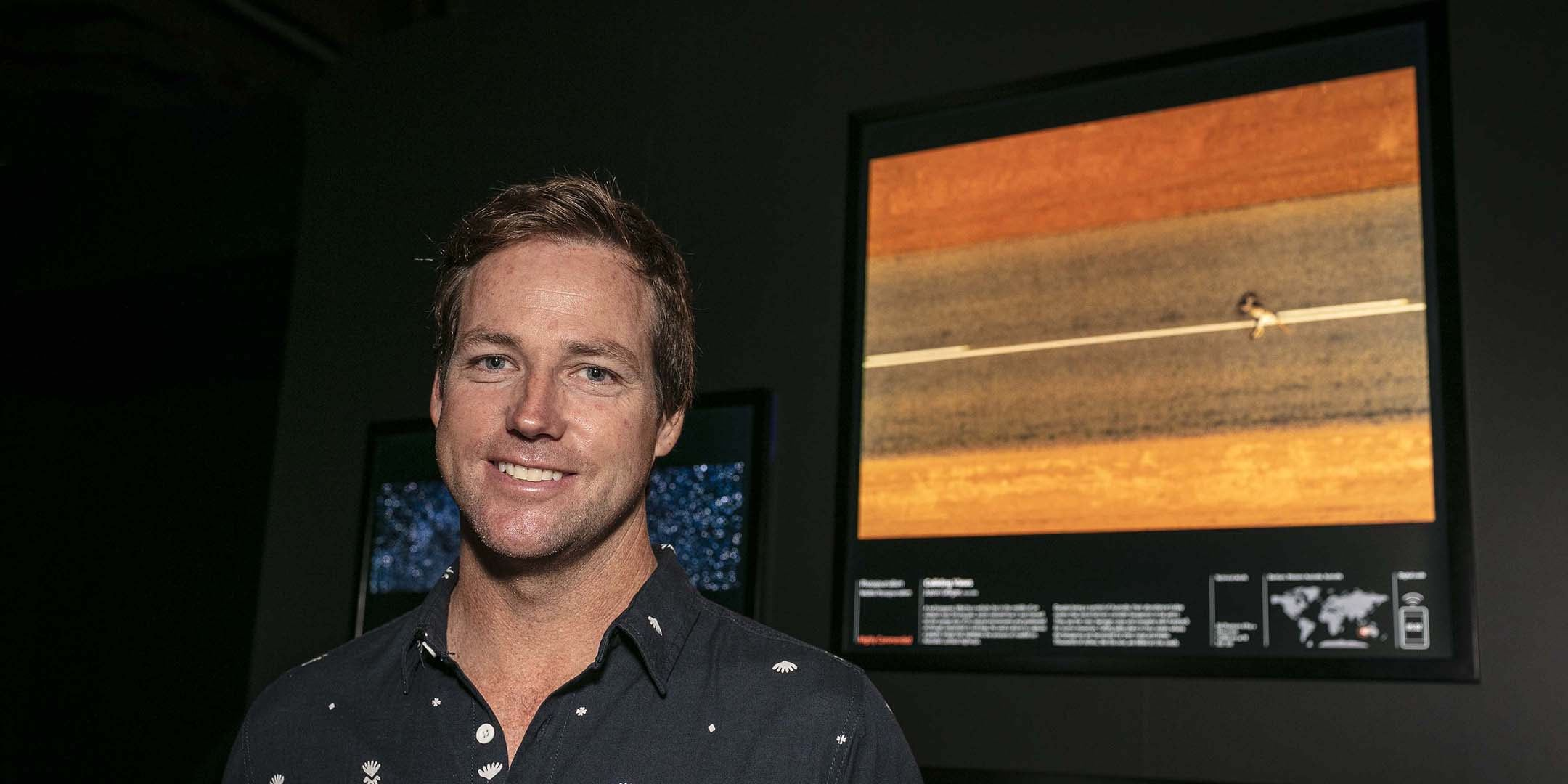Photojournalist Justin Gilligan standing in front of his photograph, Colliding Views