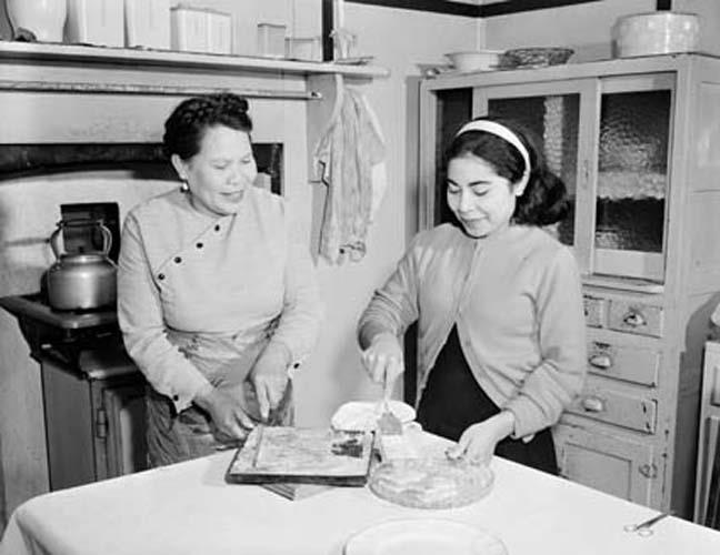 Mary Jacob helps her mother Annie O'Keefe to prepare afternoon tea, 1956. Photographer Neil Murray. Reproduced courtesy National Archives of Australia: A1501, A429/3.