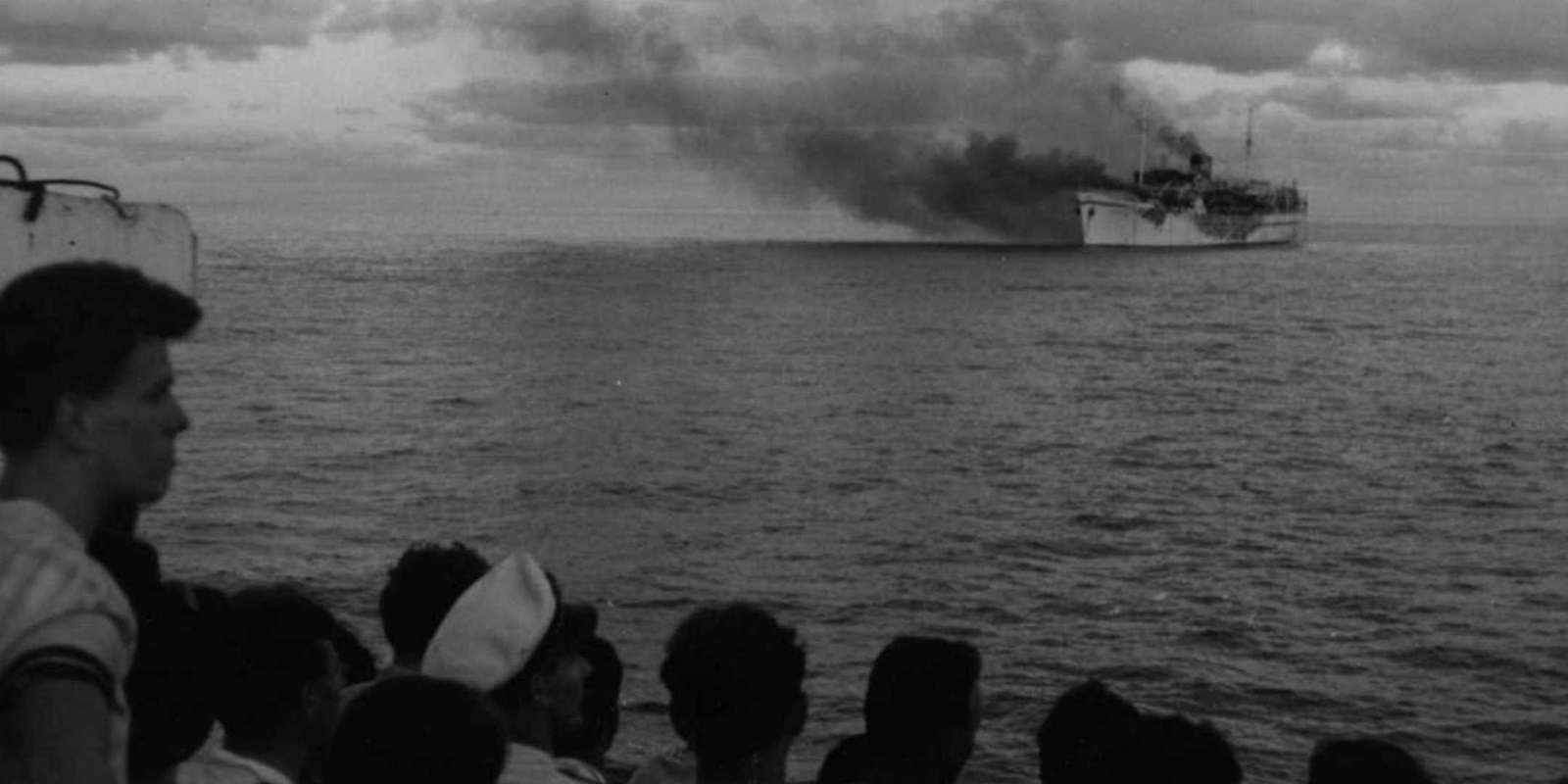 Passengers watch from the deck of City of Sydney as Skaubryn burns in the Indian Ocean, 1958. ANMM Collection Gift from Barbara Alysen ANMS0214[005]. Reproduced courtesy International Organisation for Migration