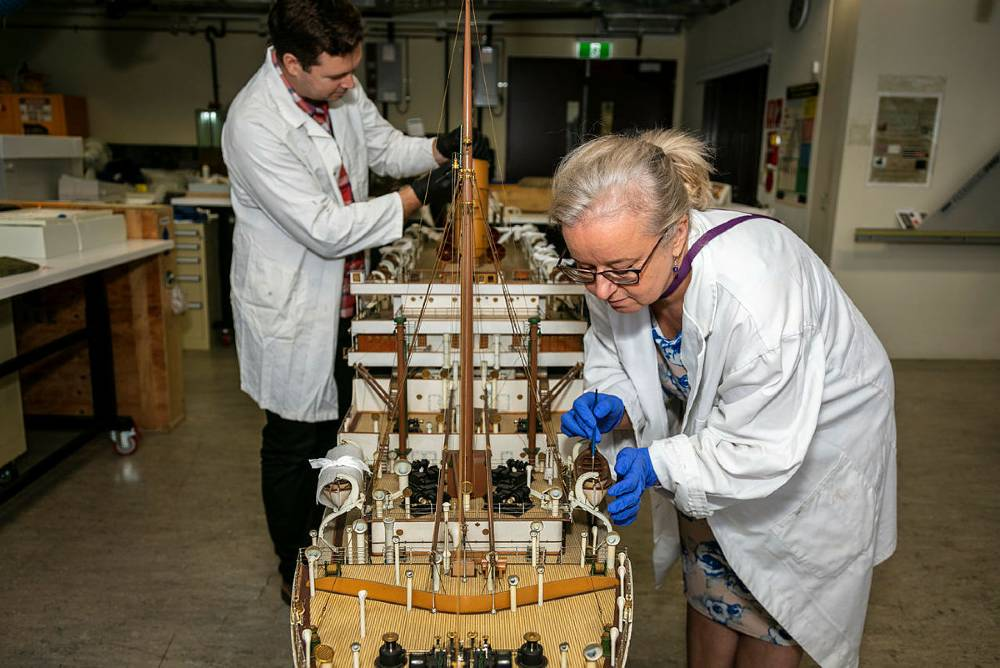 Conservators Agata Rostek-Robak and Nicholas Flood at work on the model of SS Orontes, 2019