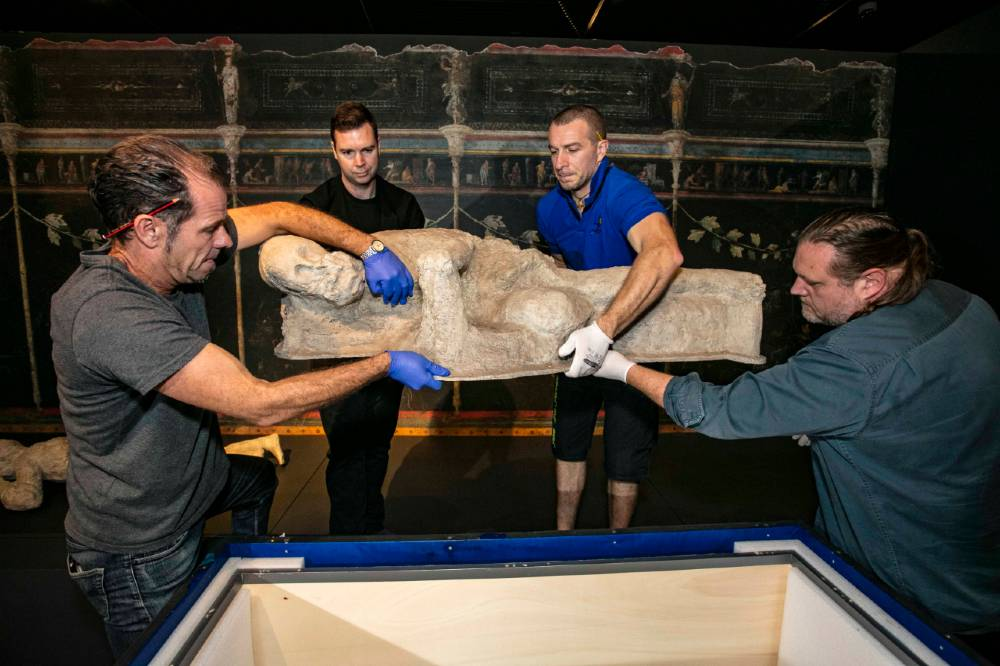 Exhibition install team members lifting one of the Pompeii figures from its packing crate