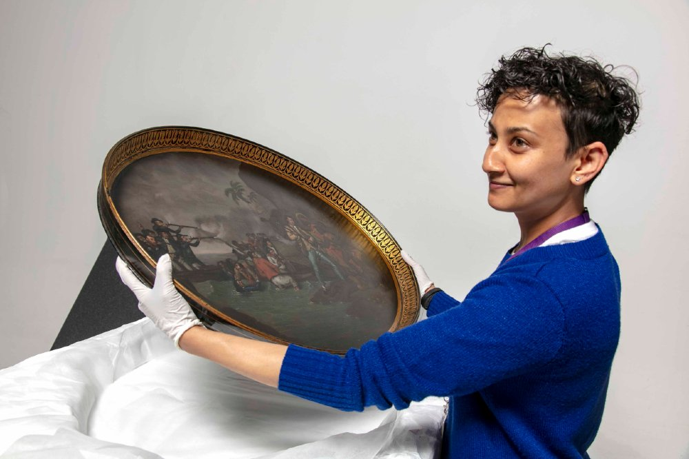 Registrar Anupa Shah unpacking a new acquisition of a tea tray dating from around 1781 painted with a scene of the death of Captain Cook.