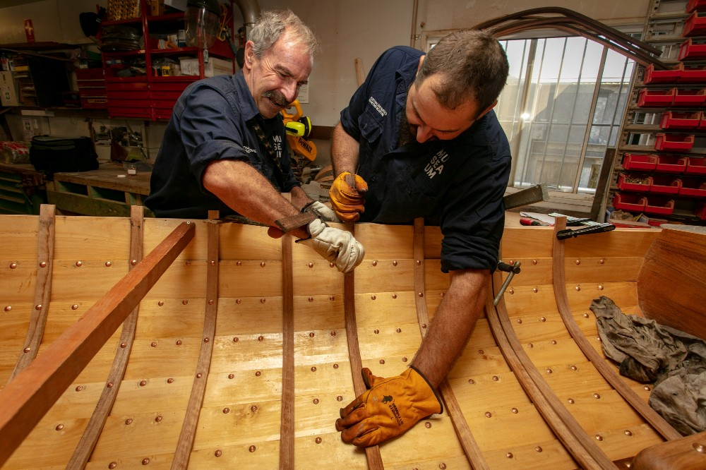 Senior Shipwright Cody Horgan and volunteer Steve steaming and fitting timber sections to a small wooden boat, February 2019