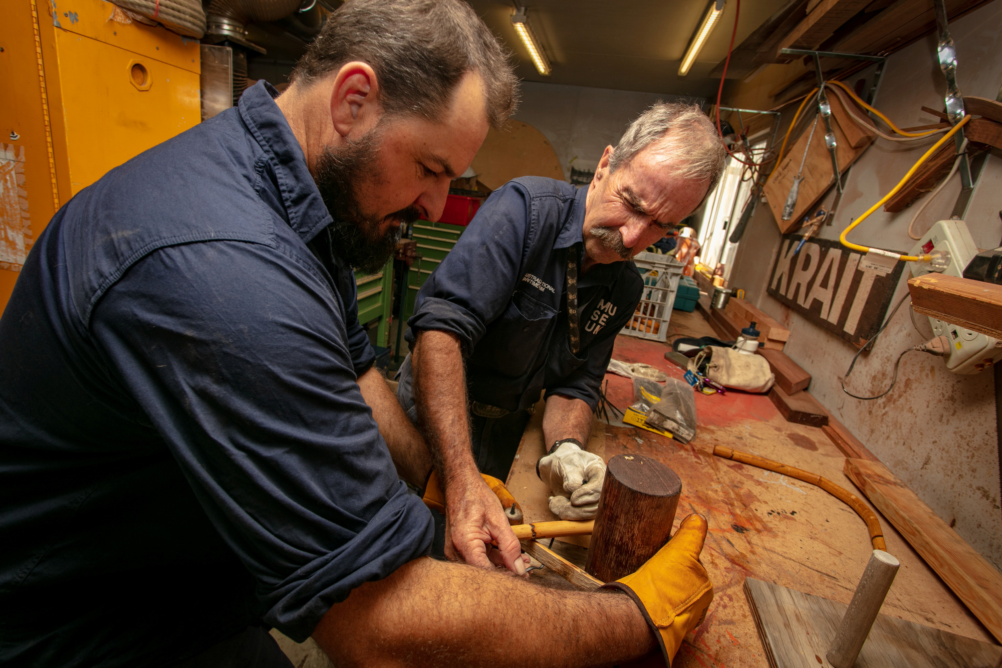 Senior Shipwright Cody Horgan and volunteer Steve fitting timber sections for a small wooden boat, February 2019