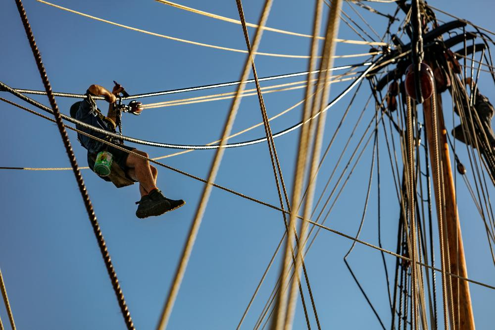 Senior Shipwright Cody Horgan painting the ropes on the replica of HMB Endeavour, 2019