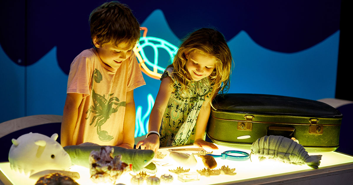 A boy and a girl interacting with objects on one of the museum touch tables
