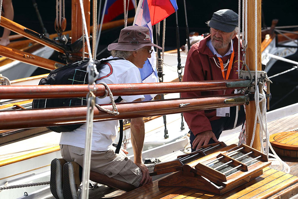 Two men in discussion on a boat on show at the Classic and Wooden Boat Festival