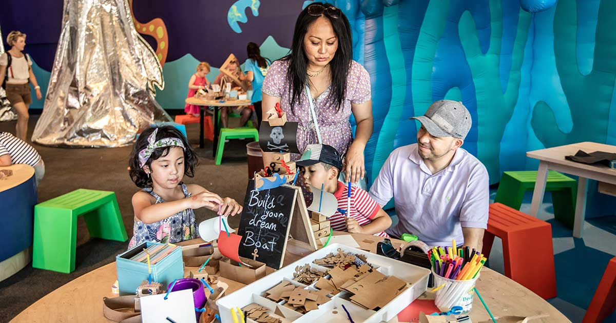 A family making craft in the museums Kids on Deck space