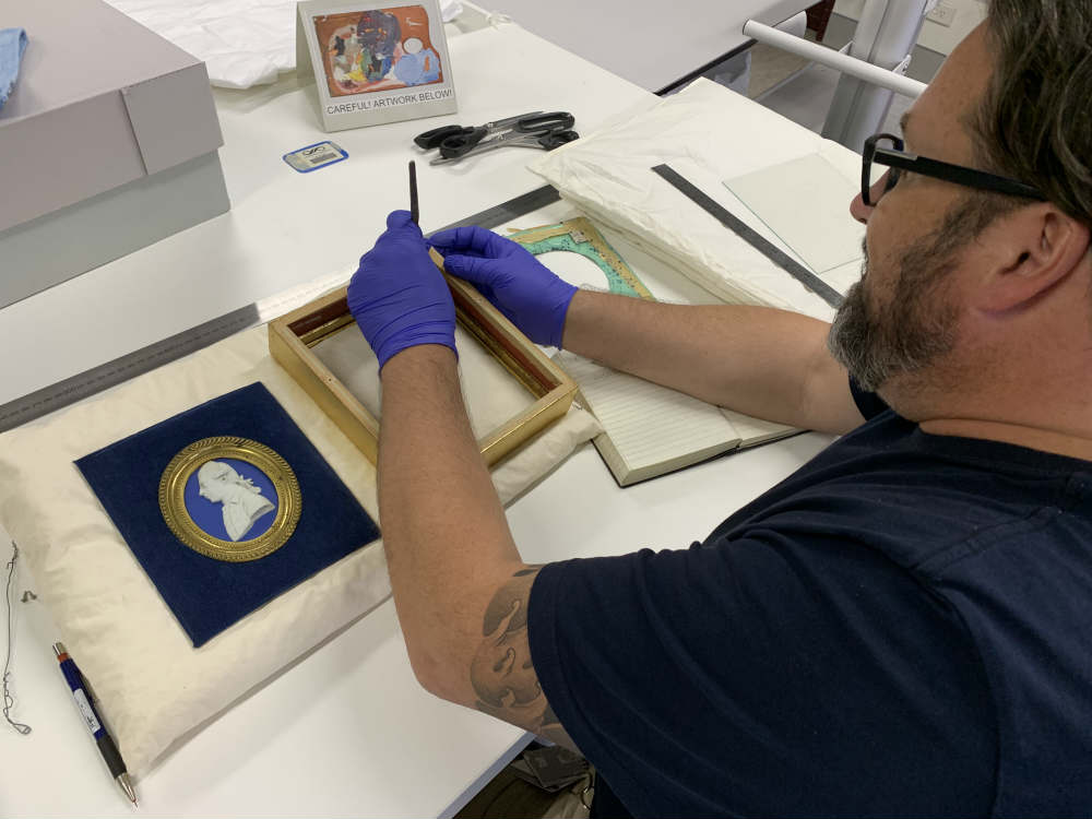Conservator Jeff Fox working on cameo. Image: ANMM