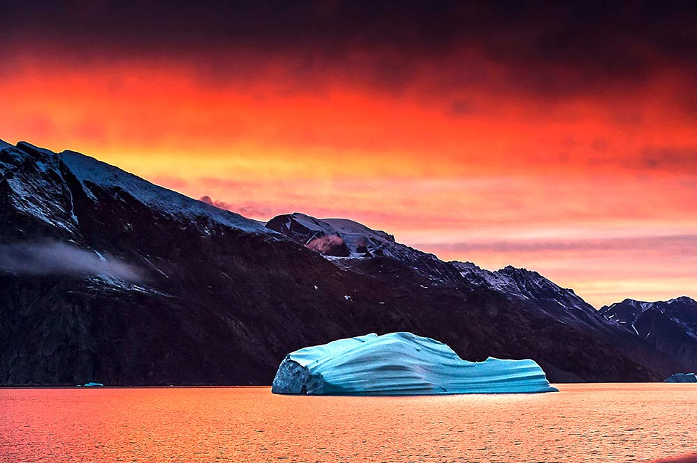 'The top of Earth is a Never-Never Land of enchanting splendour: awe-inspiring, serene and powerful, and yet maddeningly elusive. Our world's northernmost reaches play to our sense of exploration.' (Michael Aw, Principal Photographer.) The fiery colours of an Arctic sunset at Eskimobukta. Image David Doubilet, Eskimo Bay, 2015.