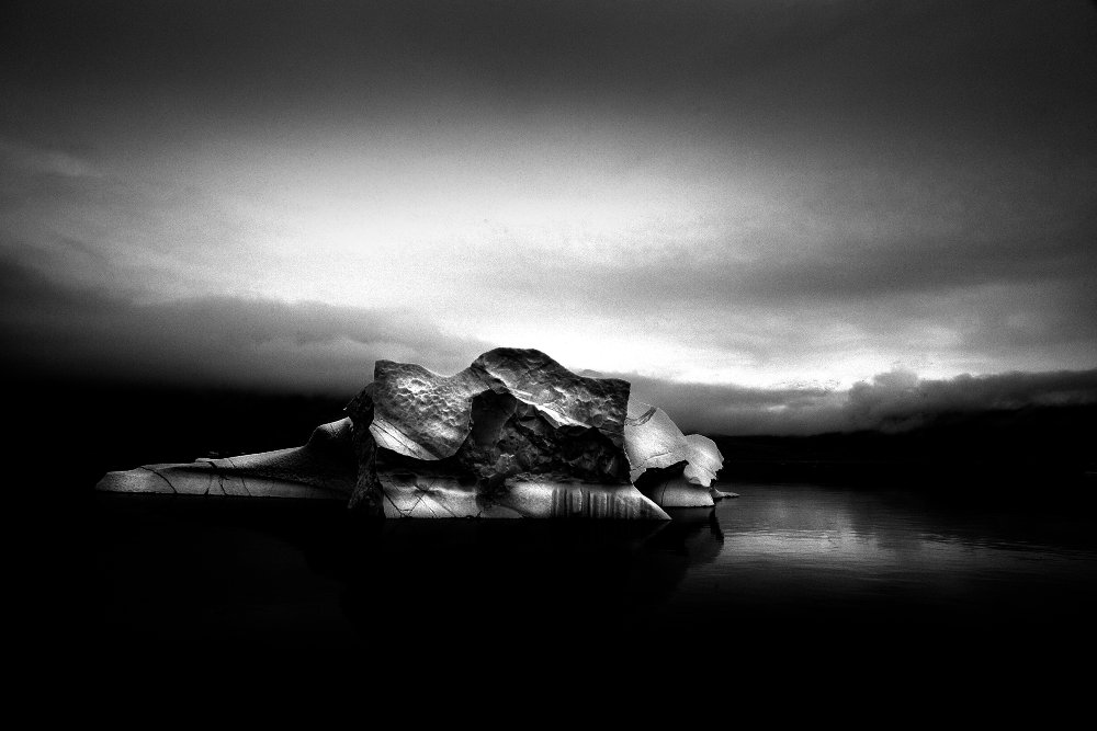 'To inquire into the intricacies of a distant landscape, then, is to provoke thoughts about one's own interior landscape, and the familiar landscapes of memory. The land urges us to come around to an understanding of ourselves.' (Barry Lopez, 'Arctic Dreams'.) Iceberg in monochrome at Harefjord. Image Ernie Brooks II, Greenland, 2015.