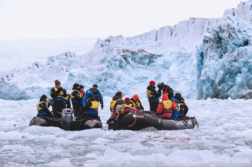 The Elysium team approaches an ice shelf in Zodiac inflatable boats, the easiest way to travel to shore. Image Jennifer Hayes, Svalbard, 2015.
