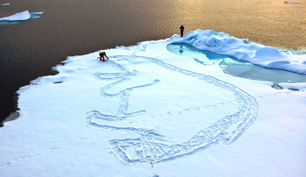 Expedition artist Wyland creates the Arctic's largest polar bear. Image Huat Seong Saw, Svalbard, 2015.