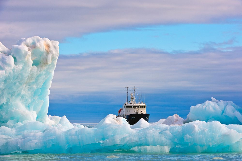 'Polar Pioneer', the Elysium Arctic expedition vessel, approaches to pick up the team. Image Michael Aw, Greenland, 2015.