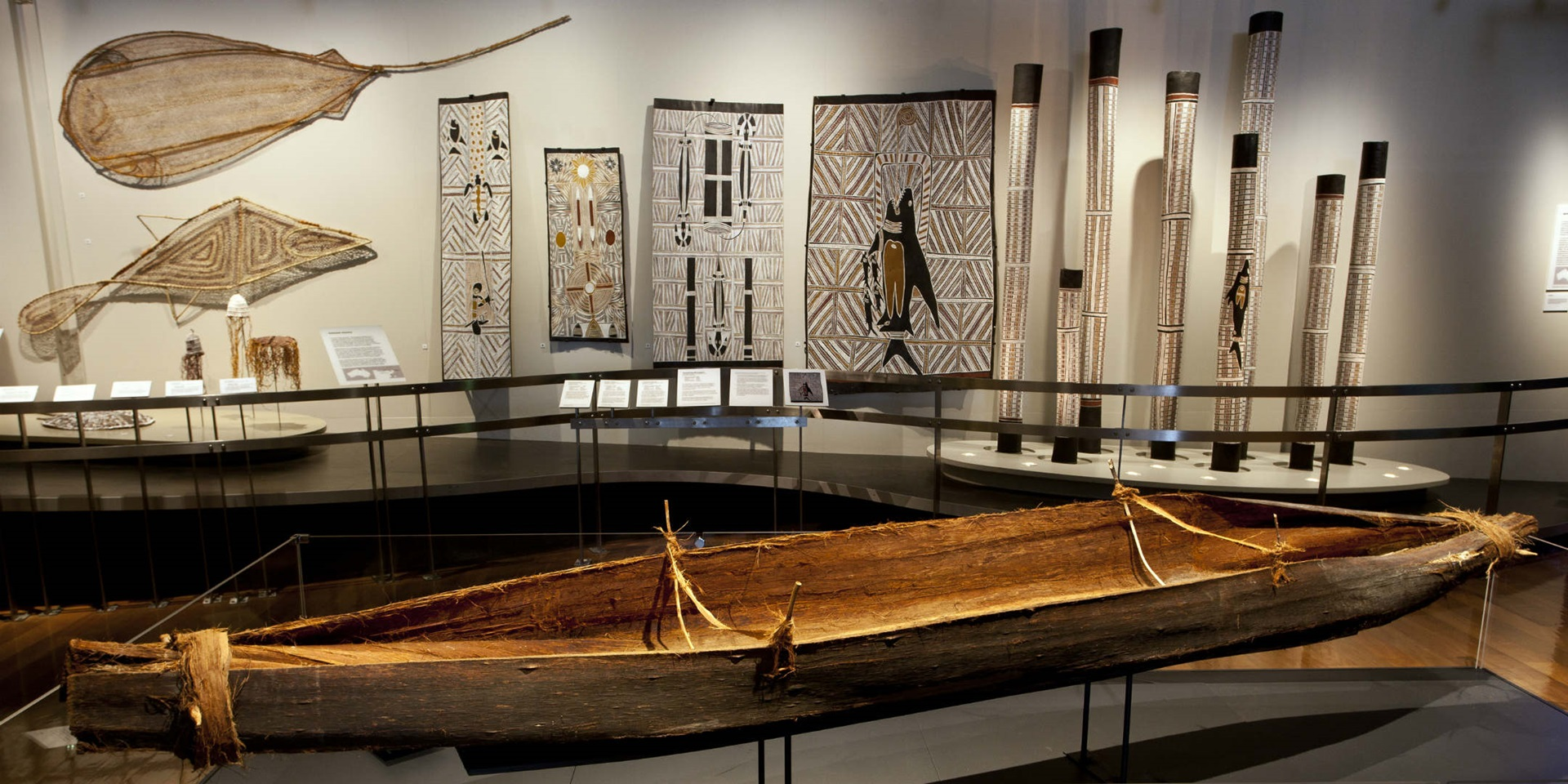 Nawi bark canoe on display in the Eora First People gallery, August 06, 2015. Featured in the background a selection of indigenous Australian woven sculptures, bark paintings and burial poles