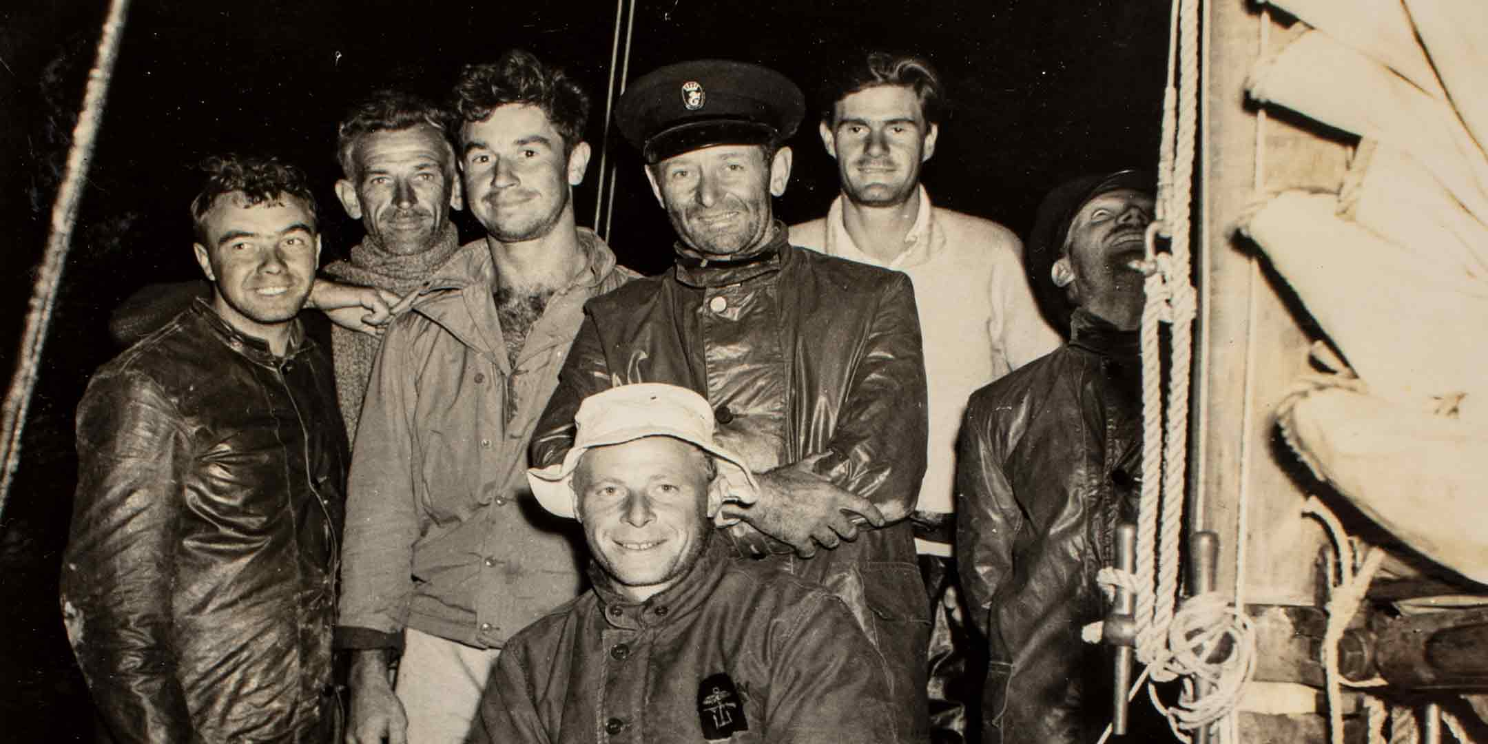 Skipper Captain John Illingworth (centre standing in cap) with the crew of Rani, the winner of the first Sydney to Hobart Yacht Race, 1.45am, 2 January 1946. ANMM Collection 00048228_003, Gift from Alison Richmond