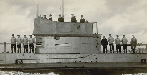 Black and white image of numerous sailors and officers posing on board the submarine HMAS AE2