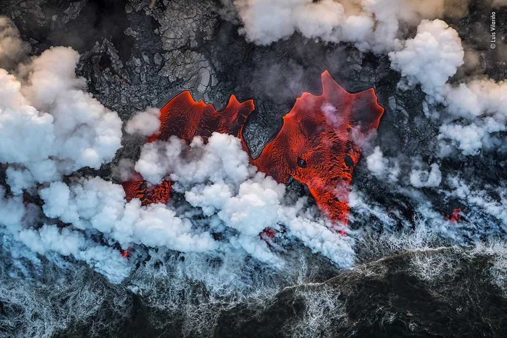 'Creation', Luis Vilariño, Spain. Red-hot lava from Kīlauea volcano instantly boils the cool Pacific Ocean where they meet at the Hawaiian coast. As Luis's helicopter flew along the coastline a sudden change in wind direction parted the plumes of steam to reveal the fiery river. Quickly framing his shot through the helicopter's open door, he captured the tumultuous creation of new land.
