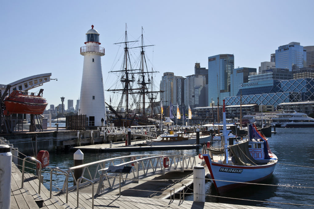Museum vessels moored at the wharves (including Vietnamese refugee boat Tu Do in foreground and Endeavour in background), with the Cape Bowling Green lighthouse, Harding safety boat, and city buildings in the background